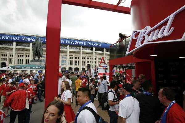 In this July 11, 2018 photo, people walk past a Budweiser pavilion in front of the Luzhniki Stadium as fans arrive for the semifinal match between Croatia and England, during the 2018 soccer World Cup in Moscow, Russia.