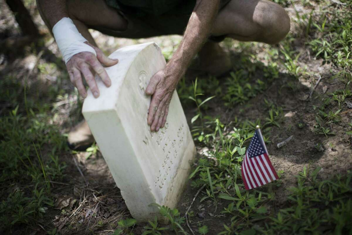 Glenn Brymer is helping restore grave markers at the Spring Peaceful Rest Cemetery in Spring.