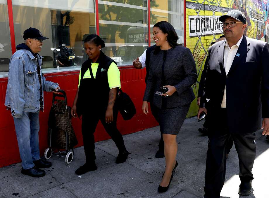 A supporter greets San Francisco Mayor London Breed, third from left, as she participates in a walking tour of the Tenderloin with Jonea Drummer, second from left, community ambassador for Mid Market/Tenderloin, Mohammed Nuru, right, Director of Public Works and other department heads on Friday, July 13, 2018, in San Francisco, Cali. Photo: Yalonda M. James / The Chronicle