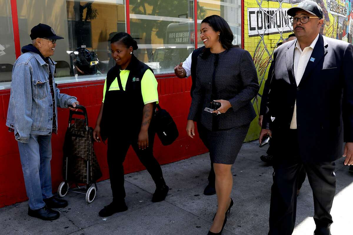Nuru (right) takes a walking tour of the Tenderloin in 2018 with Mayor London Breed and community ambassador Jonea Drummer.
