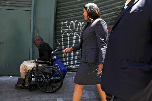 San Francisco Mayor London Breed looks at a wheelchair bound person during a walking tour of the Tenderloin with department heads on Friday, July 13, 2018, in San Francisco, Cali.