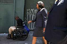 San Francisco Mayor London Breed looks at a wheelchair-bound person during a walking tour of the Tenderloin on Friday.