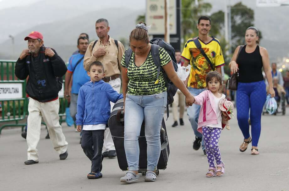 Yelitza Fuenmayor and her children cross a bridge from Venezuela to Colombia last month. Over 1 million Venezuelans have fled across the border into Colombia in less than two years. Photo: Fernando Vergara / Associated Press