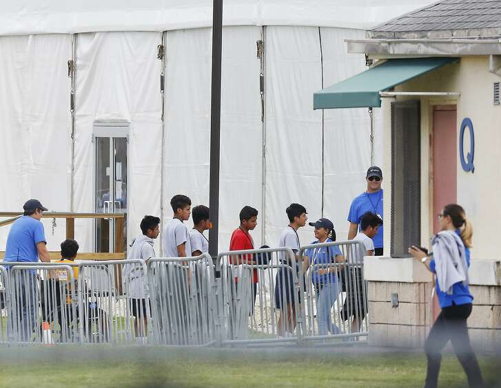 FILE - In this June 20, 2018, file photo, immigrant children walk in a line outside the Homestead Temporary Shelter for Unaccompanied Children a former Job Corps site that now houses them in Homestead, Fla. The landmark court case that has provided the framework for how the government can detain immigrant children has been cited by both sides of the debate over the separation of families at the border. The 1997 settlement known as the Flores agreement has been litigated off and on for the past 33 years and is a crucial piece of the puzzle for the administration's immigration enforcement policies. (AP Photo/Brynn Anderson, File)