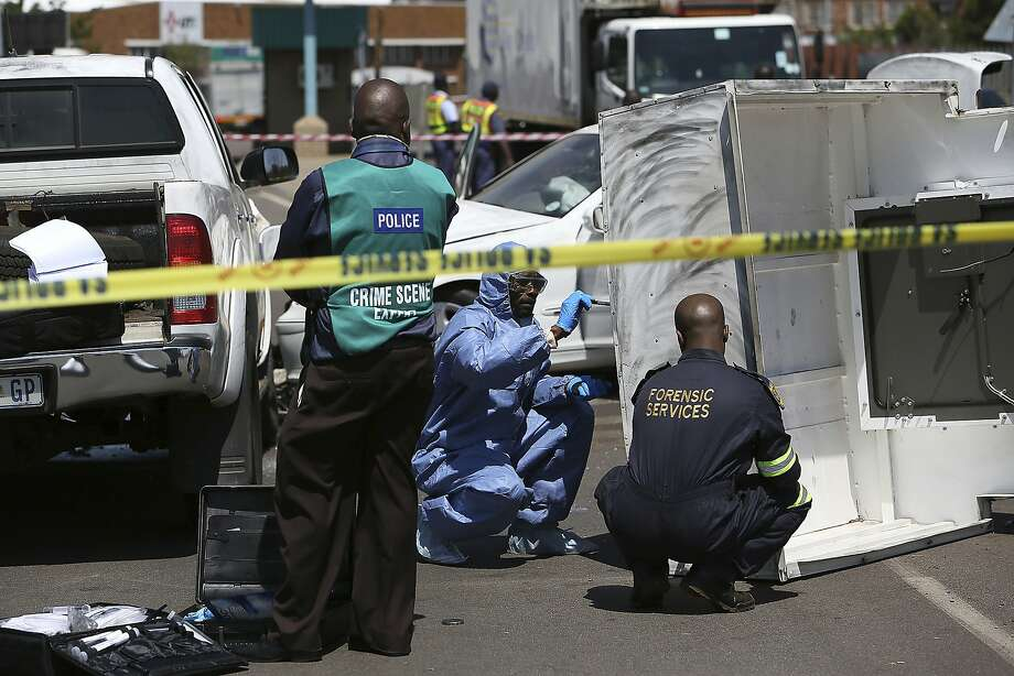 A forensics team searches for clues at the scene of a cash transit heist in 2014 in Johannesburg. Criminal syndicates are blamed for a sharp increase in the attacks this year. Photo: Associated Press 2014