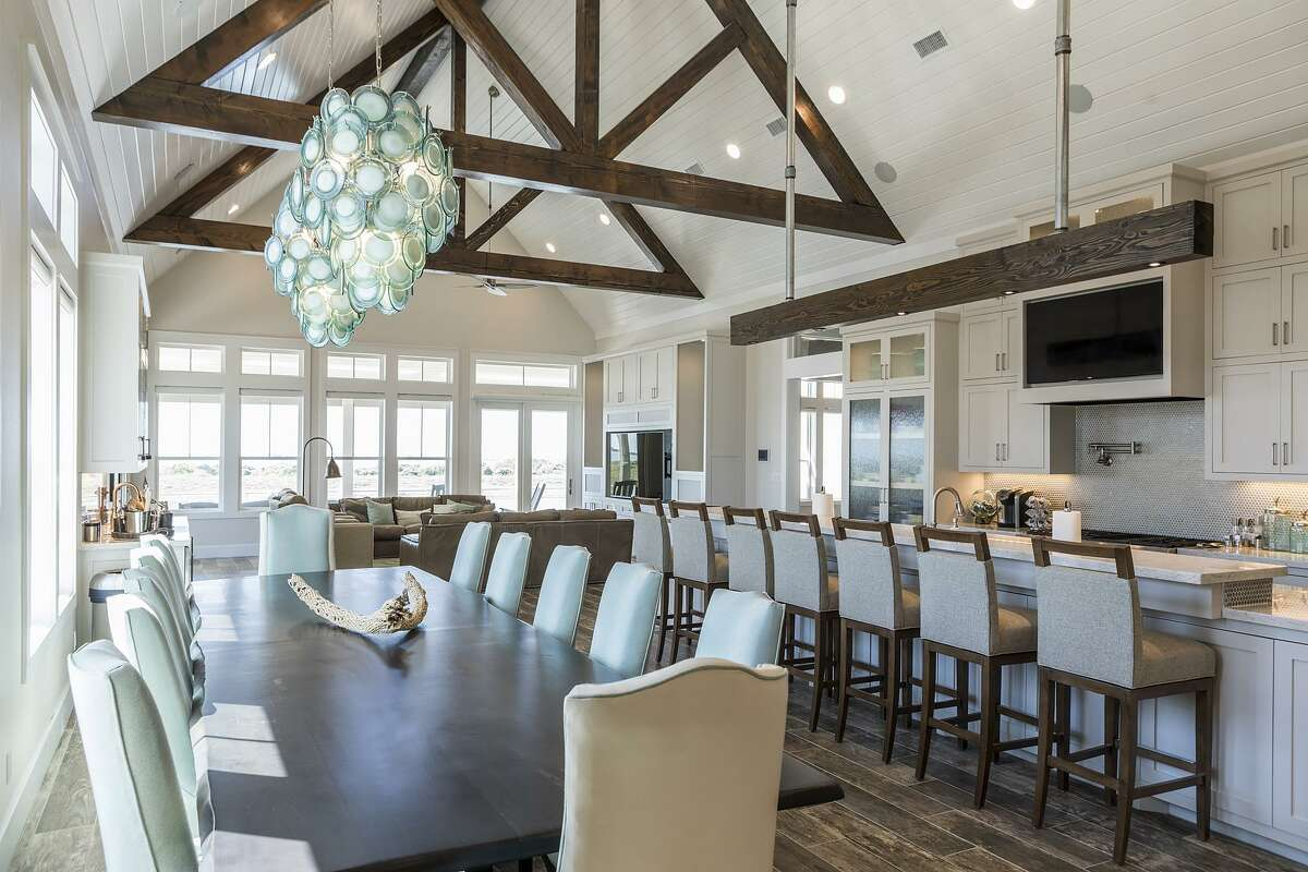 A large light fixture in seaglass green hangs over the dining table, which seats 12. The island seats seven more.