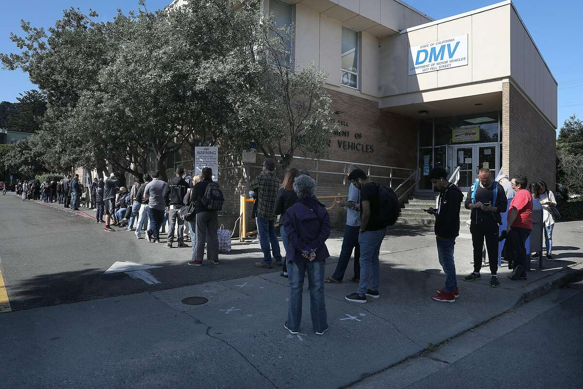 Line for the State Department of Motor Vehicles wraps around the other side of the building on Thursday, July 5, 2018 in San Francisco, Calif. YoGov, an Oakland company that promises �expedited appointments� at field offices at a time when lines at the DMV are getting longer and appointments harder to schedule.