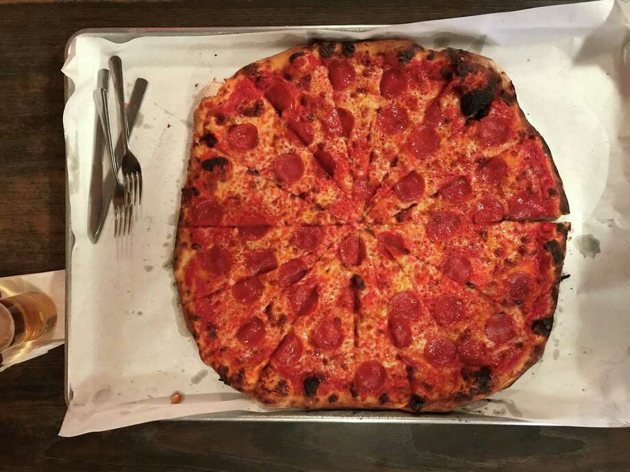 A tomato, mozzarella, and pepperoni pizza at  Sally's Apizza, 237 Wooster St., in New Haven, CT. Photo: Greg Morago / Greg Morago
