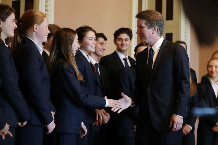 Supreme Court nominee Brett Kavanaugh shakes hands with members of the Senate Page program after posing for photographs with them at the U.S. Capitol Wednesday. Readers debate the process and the president's pick.