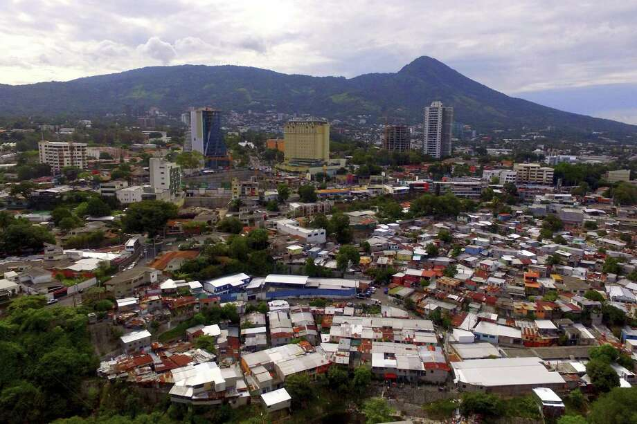 The San Salvador volcano towers over the Zona Rosa neighborhood, while hundreds of corrugated metal roof homes are piled up in a community known as Las Palmas, a territory under the control of the Barrio 18 gang in San Salvador, El Salvador. To stop the mass migration, the U.S. must step up to help countries such as El Salvador, Honduras and Guatemala deal with root causes. Photo: Salvador Melendez /Associated Press / Copyright 2018 The Associated Press. All rights reserved
