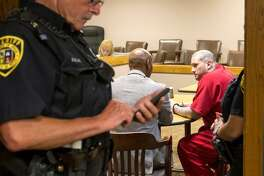 Capital murder suspect Brian Flores, right, talks in the courtroom July 5 with his second chair attorney David Woodward, after a mistrial was declared in Flores' case. Visiting Judge Susan Reed caused this when she made the second chair attorney proceed with jury selection though the first chair was unable to work because of a concussion.
