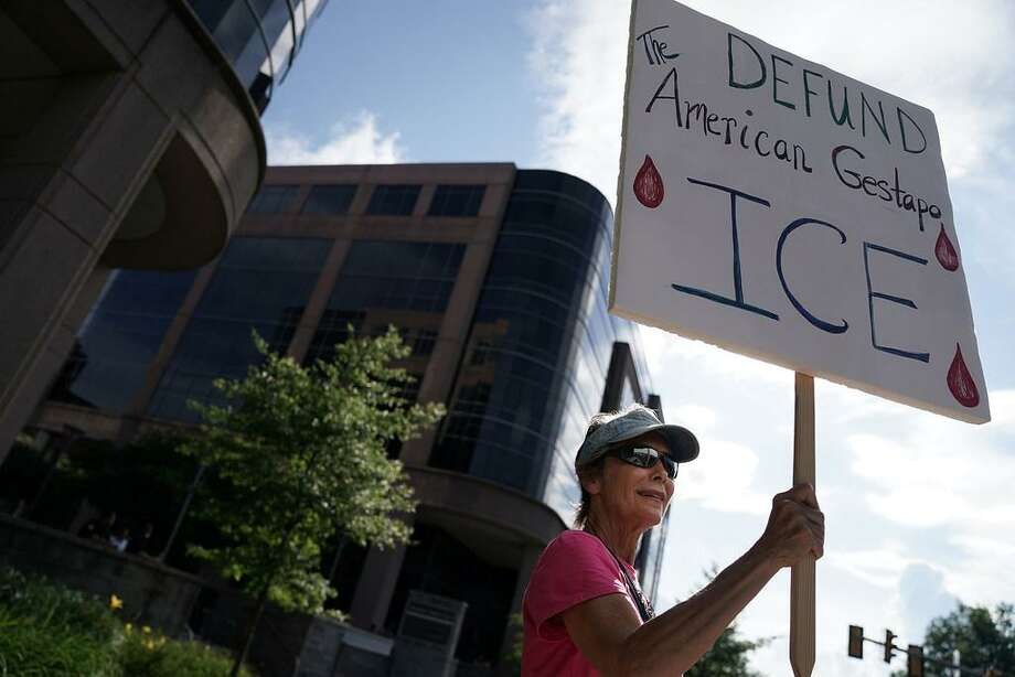 An activist holds a sign during a protest outside a U.S. Citizenship and Immigration Services field office July 5 in Fairfax, Virginia. The group No Justice No Pride staged a protest, urging the abolishment of Immigration and Customs Enforcement (ICE). Photo: /