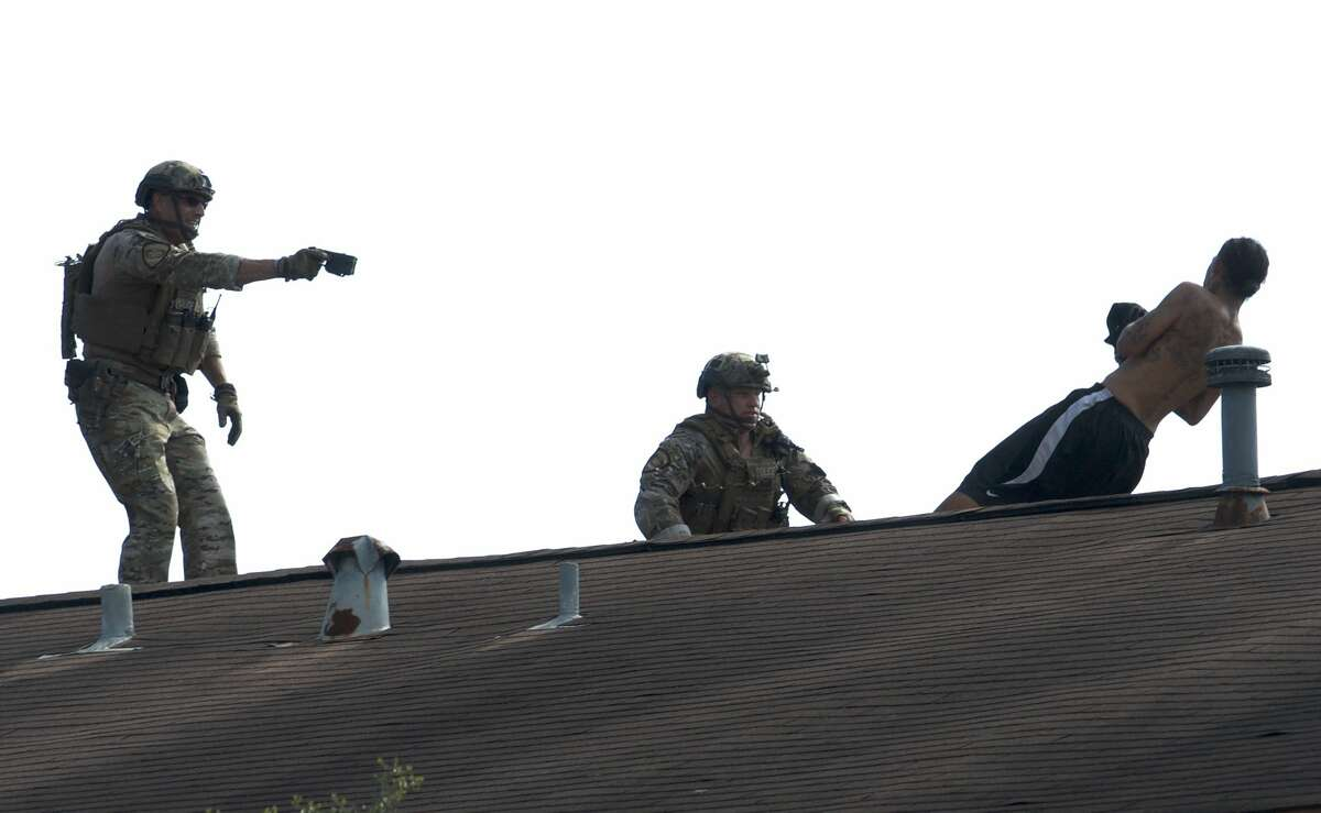 Houston Police Department SWAT officers use a stun gun on Patrick Torres, 34, who allegedly held two women hostage and then refused to come down from an apartment complex roof Friday, July 13, 2018.