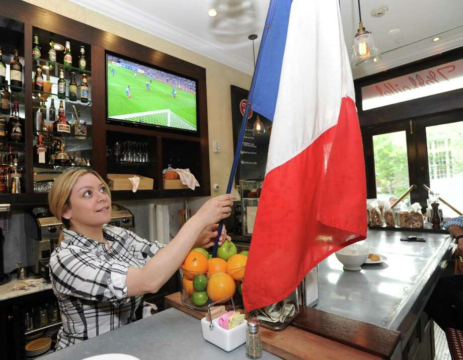 Waitress Chantelle Salamanca, left, raises the French flag while watching the Euro 2016 semi-final soccer match between France and Germany at Bistro Versailles Patisserie in Greenwich. Photo: Bob Luckey Jr. / Hearst Connecticut Media File Photo / Greenwich Time