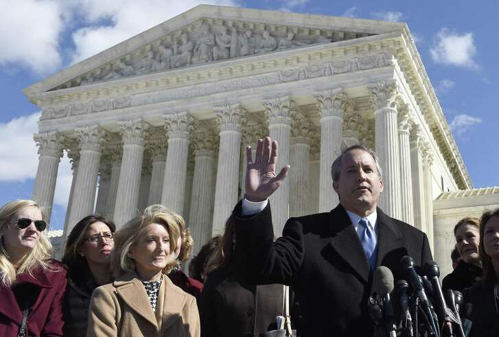 Texas Attorney General Ken Paxton, right, speaks to reporters outside the Supreme Court in Washington, Wednesday, March 2, 2016, after the court heard arguments  over Texas abortion clinic regulations in its biggest abortion case in nearly a quarter-century.  Texas State Rep. Jodie Laubenberg, listens, third from left. (AP Photo/Susan Walsh)