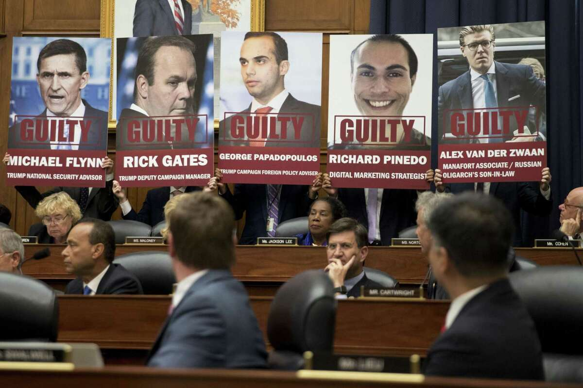 Posters of people who have plead guilty in special counsel Robert Mueller's probe into Russian interference in the U.S. elections are held by staff members during a joint House Judiciary, Oversight and Government Reform Committees hearing with FBI agent Peter Strzok. MUST CREDIT: Bloomberg photo by Andrew Harrer