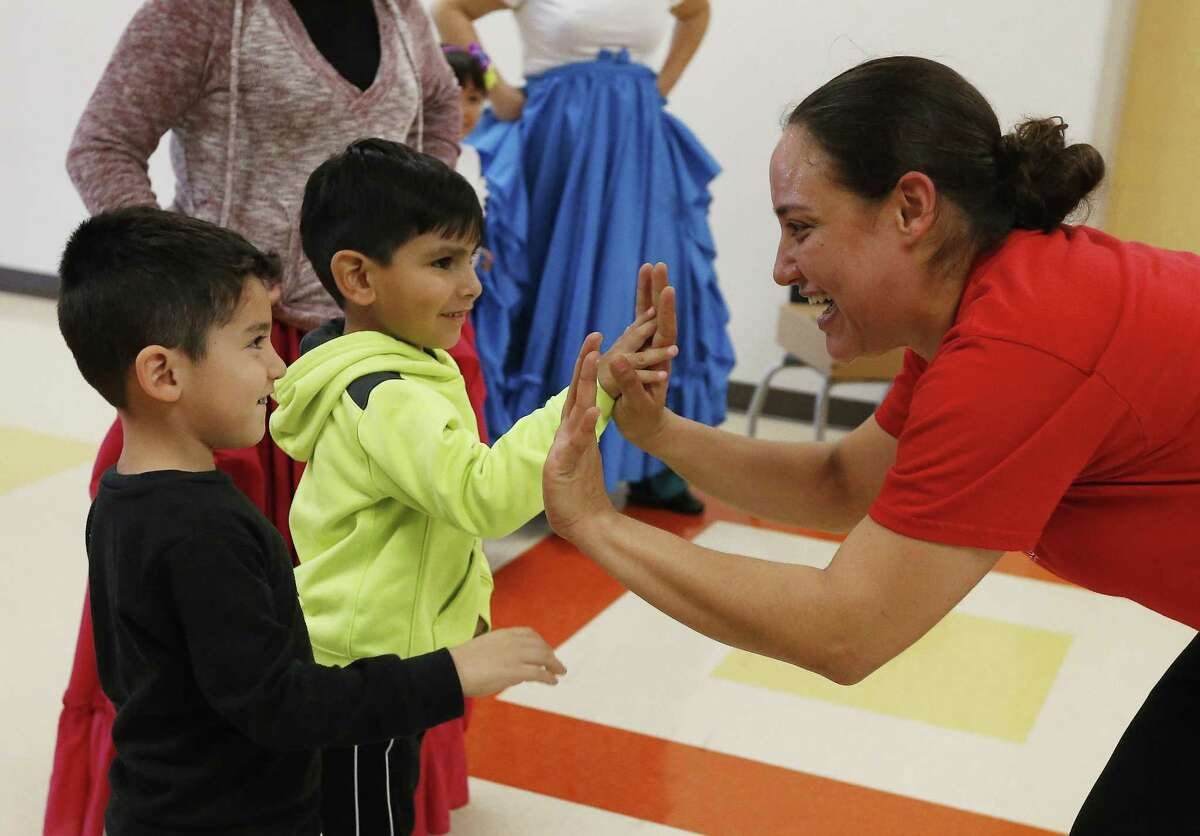 Dance instructor Marlene Pita offers high-fives to students Juan Jose (left) and Israel while leading her young students and their parents during a ballet folklorico class at Pre-K 4 SA South Education Center on Wednesday, Feb. 24, 2016. Pita leads about 14 students in the dance class twice a week which is in addition to the children's basic education classes. Pita has been a folklorico dancer for 20 years and is a member of the Guadalupe Dance Company. (Kin Man Hui/San Antonio Express-News)