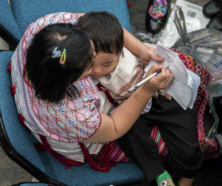 "One of the 6500 worshipers from 78 congregations including 532 of the Karen refugees takes notes as her child sleeps during the annual regional ""Be Courageous"" convention of Jehovah's Witnesses at the Times Union Arena Friday  July 13, 2018 in Albany, N.Y. (Skip Dickstein/Times Union) Photo: SKIP DICKSTEIN / 20044343A"