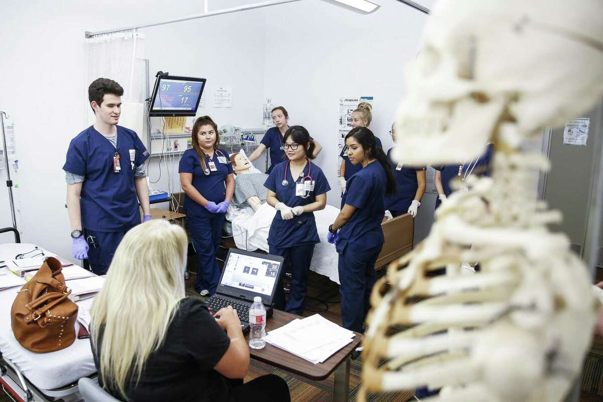 UT Health School of Nursing students listen to their instructor before working through a simulation with a mannequin July 13, 2018 in Houston. Even though male nurses make up between 10 and 12 percent of the overall nursing population in the United States, a new study contends that male nurses, on average across disciplines, make about $6,600 more annually than women doing the same job.