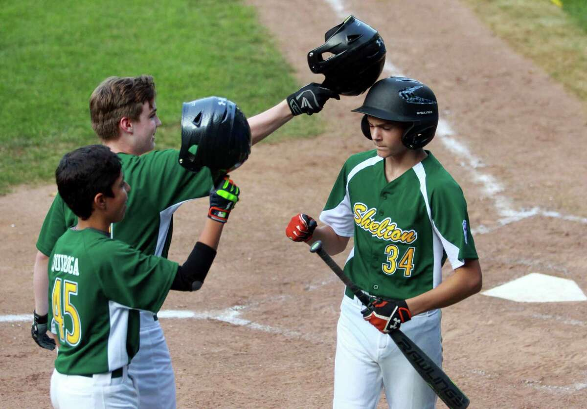 Shelton American's Ayden Sepkaski gets a tap on his helmet by teammate Jacob Giard after he hit a home run during the District 3 Little League championship game against Union City on Friday. Shelton American won 5-1.