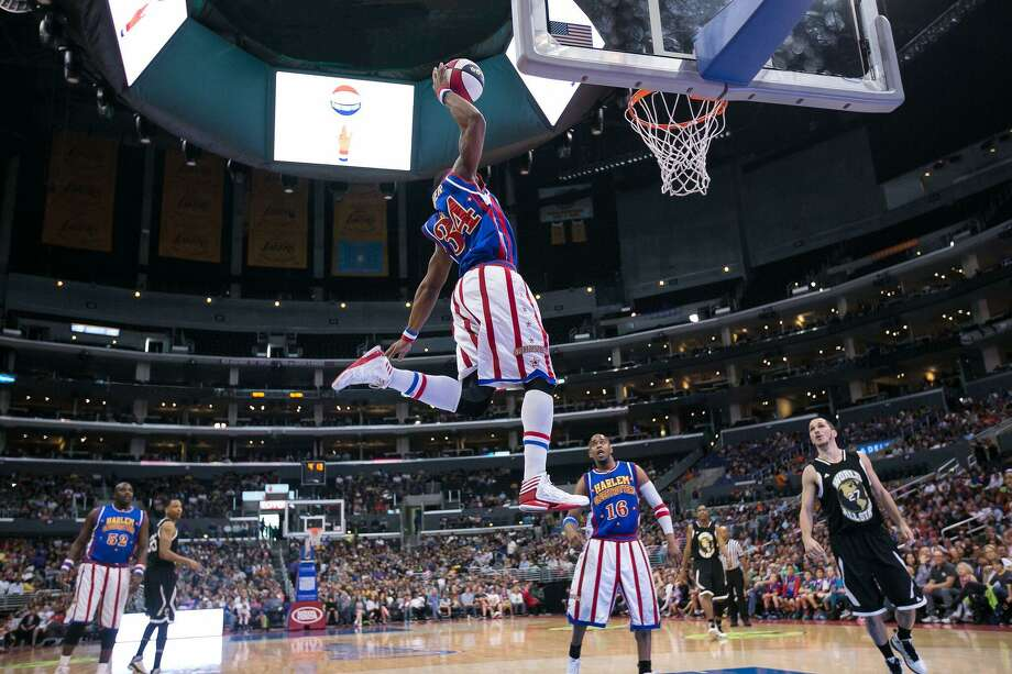"""Corey """"Thunder"""" Law is a five-year veteran of the Harlem Globetrotters (here seen finishing one of his patented, high-flying dunks), and famously made a trick shot from the roof of NRG Stadium last time he and the team came to Houston. Photo: C/o Harlem Globetrotters / HCN"""