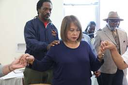 Perlita Romero (middle), wife of 61 year old security guard Rolando Romero, who was shot dead while patrolling the Alice Griffith apartments prays with members of the Bayview on Friday, July 13, 2018 in San Francisco, Calif.
