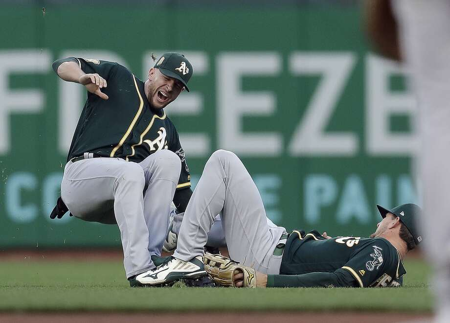 Oakland Athletics second baseman Jed Lowrie, left, collides with right fielder Stephen Piscotty after Lowrie caught a fly ball from San Francisco Giants' Alen Hanson during the third inning of a baseball game Friday, July 13, 2018, in San Francisco. (AP Photo/Marcio Jose Sanchez) Photo: Marcio Jose Sanchez / Associated Press