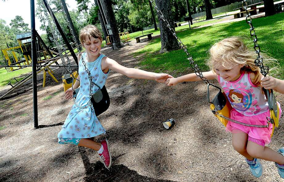 Danielle Powers, 11, tries to hold hands with Nevaeh Lofton, 4, as they play on the swings in Pirate Pride Park while also stopping at the library to get new books for a summer reading challenge. Vidor Rocks is helping raise money to try and renovate the park. The city is considering reaching out to KaBOOM!, a national organization that has offered funds to help rebuild Southeast Texas parks in the wake of Harvey. Friday, July 13, 2018 Kim Brent/The Enterprise Photo: Kim Brent / The Enterprise / BEN