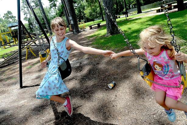 Danielle Powers, 11, tries to hold hands with Nevaeh Lofton, 4, as they play on the swings in Pirate Pride Park while also stopping at the library to get new books for a summer reading challenge. Vidor Rocks is helping raise money to try and renovate the park. The city is considering reaching out to KaBOOM!, a national organization that has offered funds to help rebuild Southeast Texas parks in the wake of Harvey. Friday, July 13, 2018 Kim Brent/The Enterprise