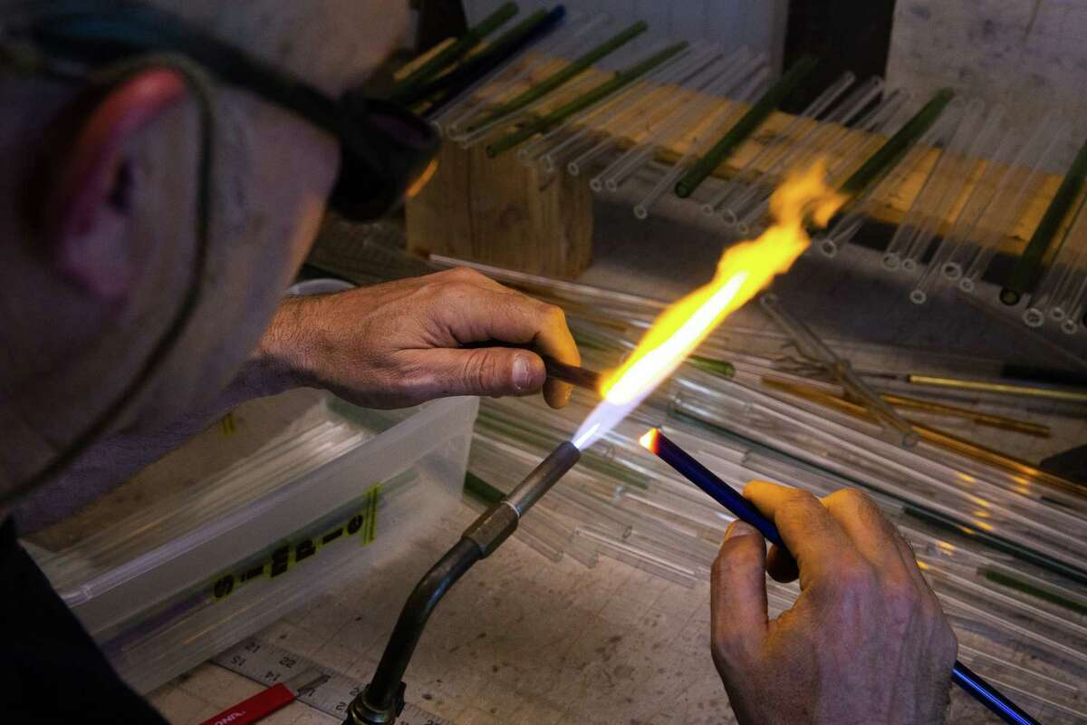 A worker uses a propane torch to polish a glass straw at the EcoGlass Straws manufacturing facility in Hood River, Oregon, on July 5, 2018.