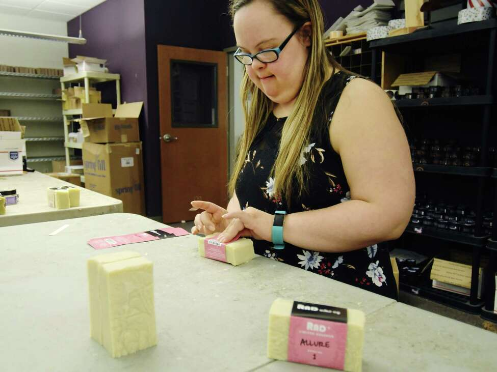 Alexis Kerber, inventory manager at the RAD Soap Co., puts labels on bars of soap in the shipping department on Wednesday, July 11, 2018, in Menands, N.Y. (Paul Buckowski/Times Union)