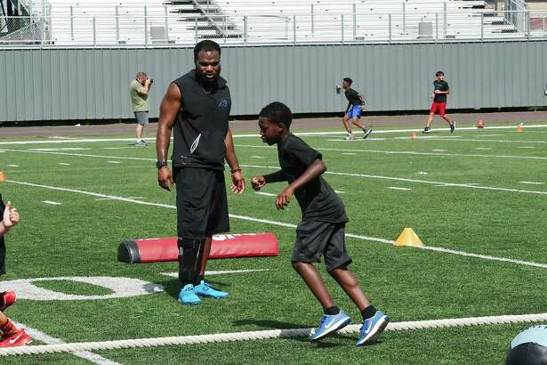 Fozzy Whittaker watches as Ryan Williams participates in a speed and conditioning drill at summer football camp Saturday at The Rig.