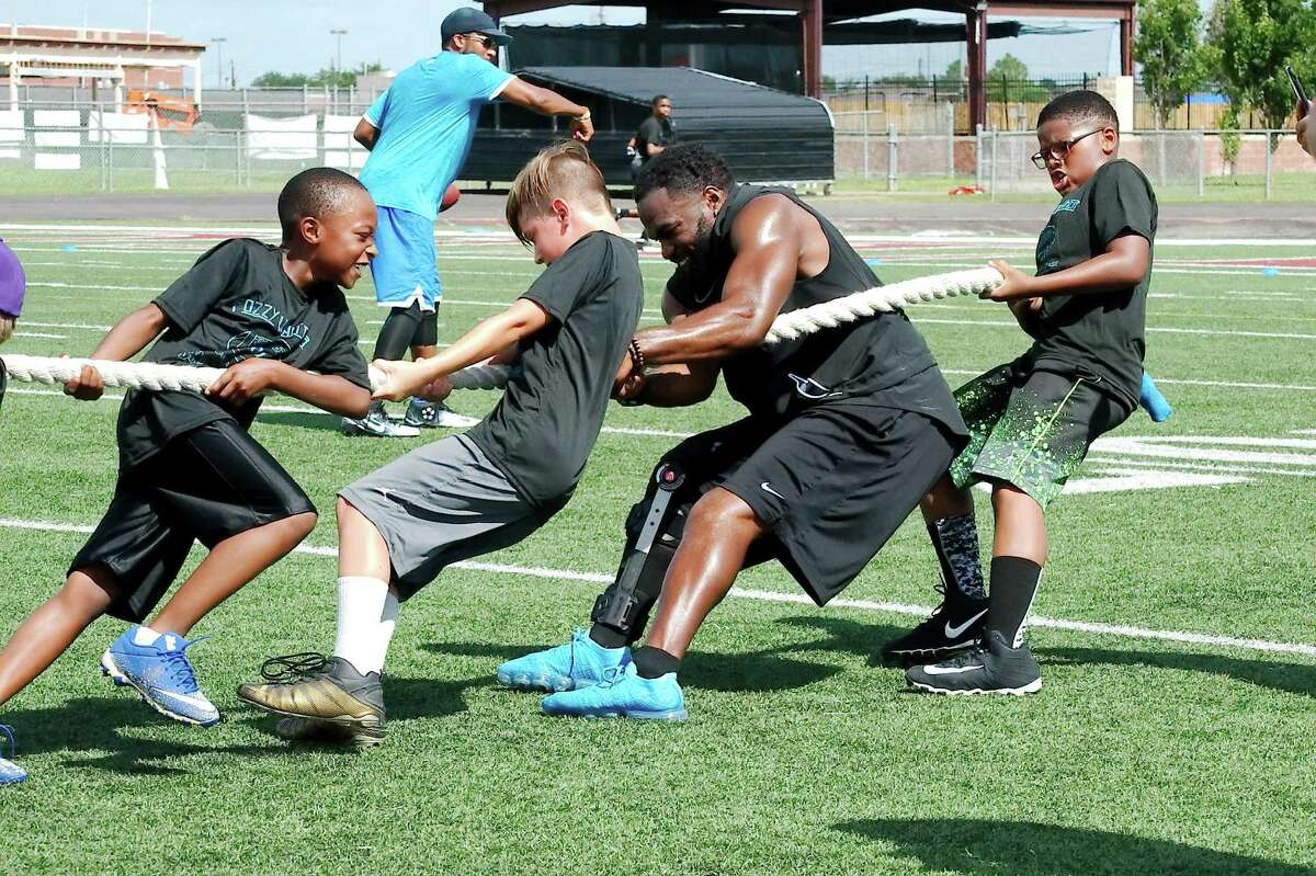 Daren Bolden (from left) Ty Stoval and Seth Groves pull with Fozzy Whittaker during a tug-of-war competition Saturday at The Rig.
