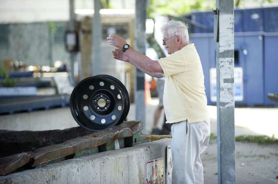 Stamford resident Bruce Huffine throws a wheel disc into a dumpster at the Mygatt Recycling Center on Magee Ave. in Stamford, Conn. on Thursday, July 12, 2018.  The city just renegotiated its contract with the recycling company it uses and now the budget will take an unexpected $700,000 hit. Photo: Michael Cummo / Hearst Connecticut Media / Stamford Advocate