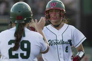 The Woodlands' Alayis Seneca gets a high-five from Lindsey Fischkelta after scoring on Abby Jones' RBI single during the first inning of Game 1 in a Region II-6A quarterfinal series on Thursday, May 10, 2018, in The Woodlands. The Woodlands defeated Rockwall 2-1.