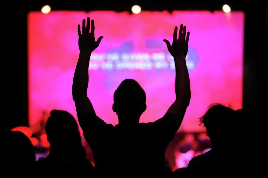 "A churchgoer raises his hands while singing along to the song ""I Love You Lord"" during a Hillsong Church service in the Wall Street Theater in Norwalk on July 8. This was the church's fourth service in the theater after establishing a branch in Norwalk. Photo: Michael Cummo / Hearst Connecticut Media / Stamford Advocate"