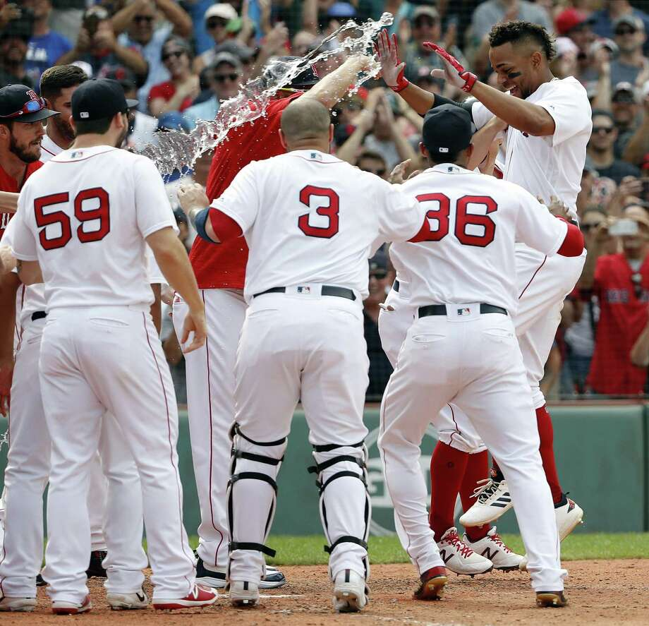 Xander Bogaerts, right, is greeted by teammates at home plate after hitting a grand slam in the 10th inning against the Blue Jays on Saturday. Photo: Winslow Townson / Associated Press / Copyright 2018 The Associated Press. All rights reserved.