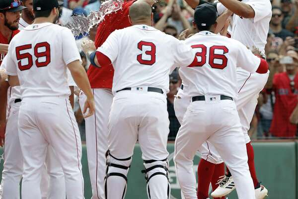 Xander Bogaerts, right, is greeted by teammates at home plate after hitting a grand slam in the 10th inning against the Blue Jays on Saturday.