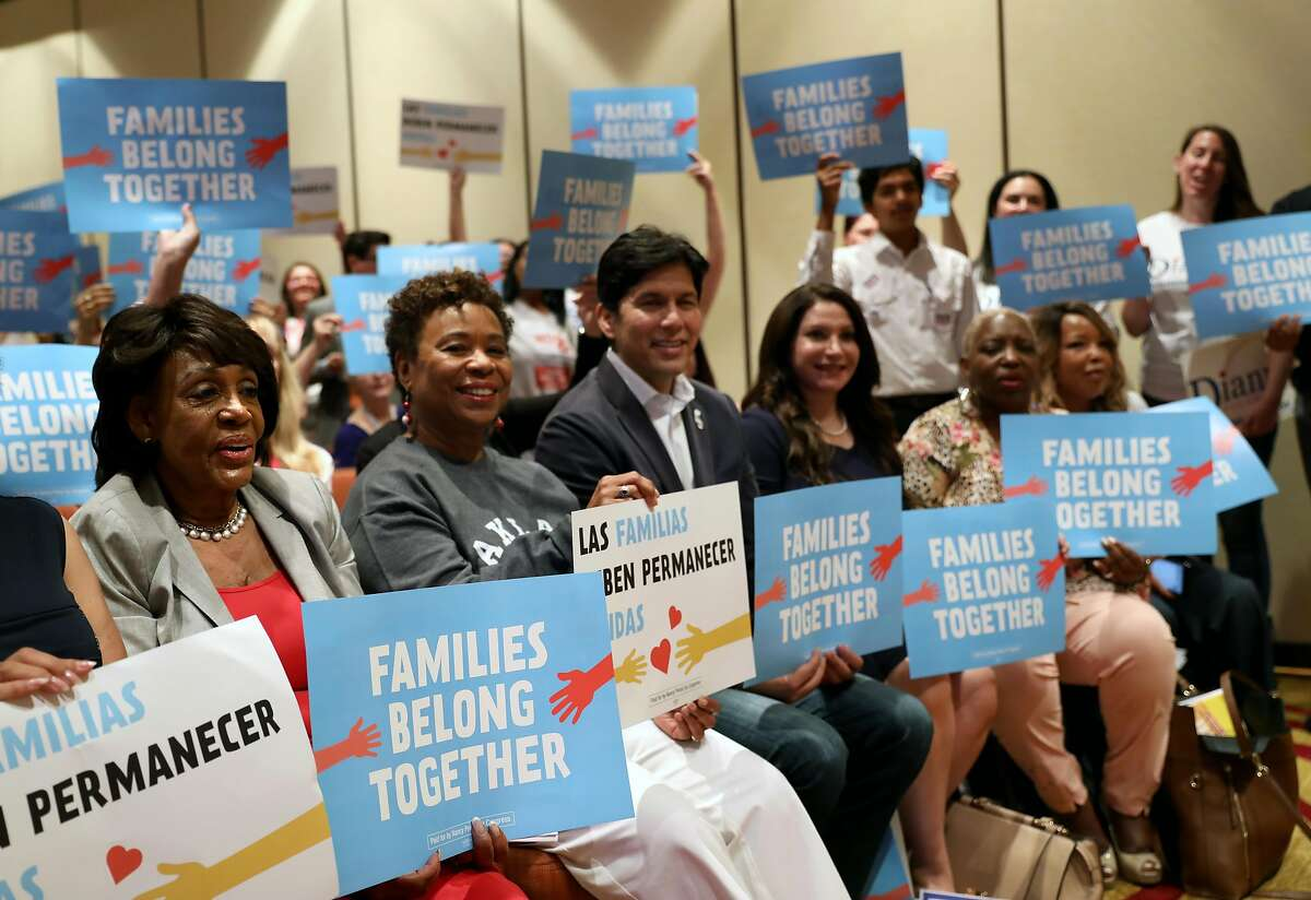 """(From left to right) U.S. Representative Maxine Waters (D-CA 43rd District), Congresswoman Barbara Lee, State Sen. Kevin de Leon, and Susan Rubio, an educator running for state senate, raise """"Families Belong Together"""" signs for a photo opportunity during the 2018 Summer Executive Board Meeting, hosted by the California Democratic Party, at the Oakland Marriott City Center on Saturday, July 14, 2018, in Oakland, Cali."""