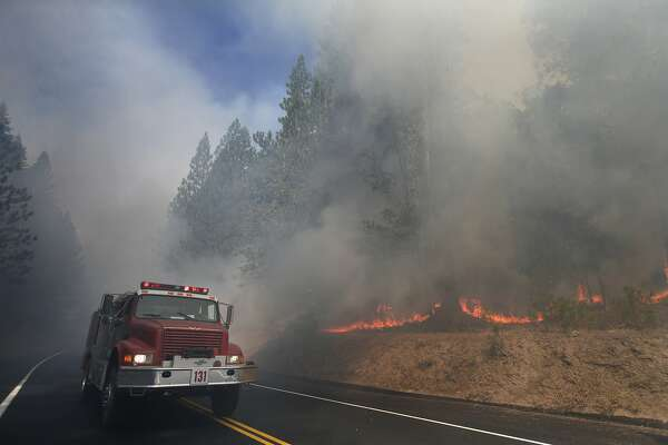 FILE - In this Aug. 26, 2013 file photo, a fire truck drives past burning trees as firefighters continue to battle the Rim Fire near Yosemite National Park, Calif. The California Department of Forestry and Fire Protection says a firefighter has been killed while battling a wildfire near Yosemite National Park. Officials say Heavy Fire Equipment Operator Braden Varney was killed Saturday, July 14, 2018, morning while battling the Ferguson Fire. The fire broke out around 10:30 p.m. Friday night in Mariposa County, near the west end of Yosemite National Park and the Sierra National Forest. (AP Photo/Jae C. Hong, File)
