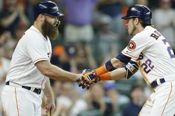 HOUSTON, TX - JULY 14:  Josh Reddick #22 of the Houston Astros shakes hands with Evan Gattis #11 after hitting a home run in the fifth inning against the Detroit Tigers at Minute Maid Park on July 14, 2018 in Houston, Texas.  (Photo by Bob Levey/Getty Images)