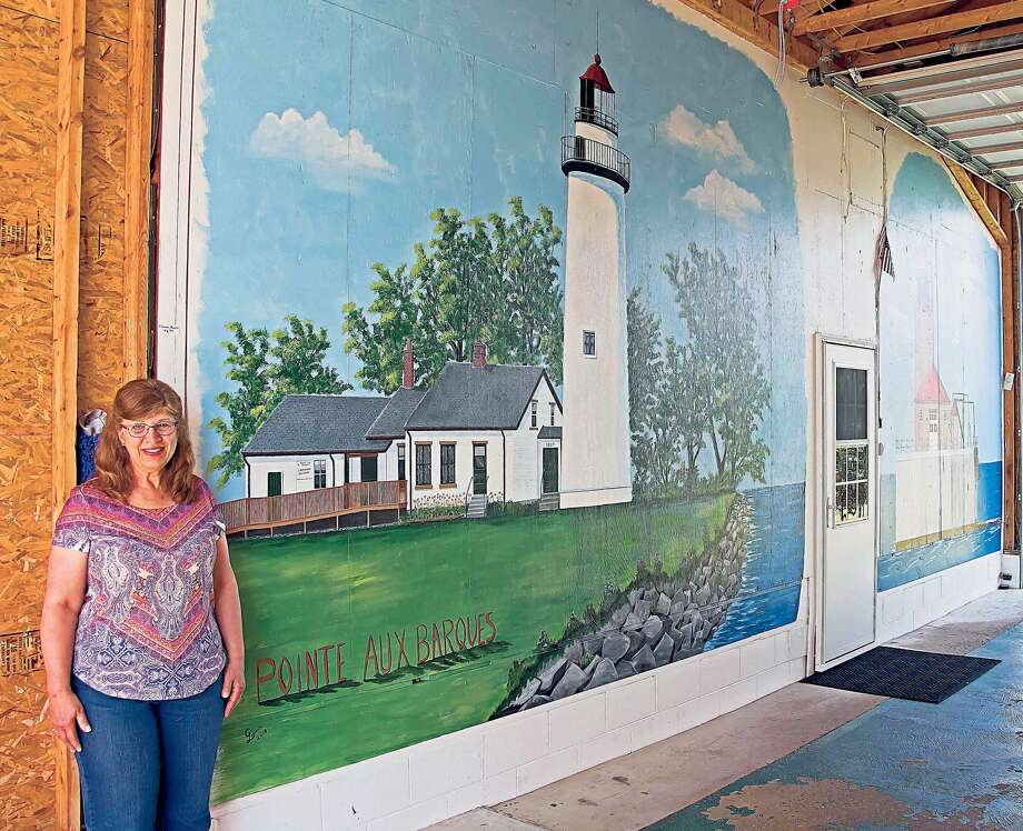 Cherie Lepeak standing beside her mural of the Port Austin Reef Lighthouse. Photo: Bill Diller/For The Tribune