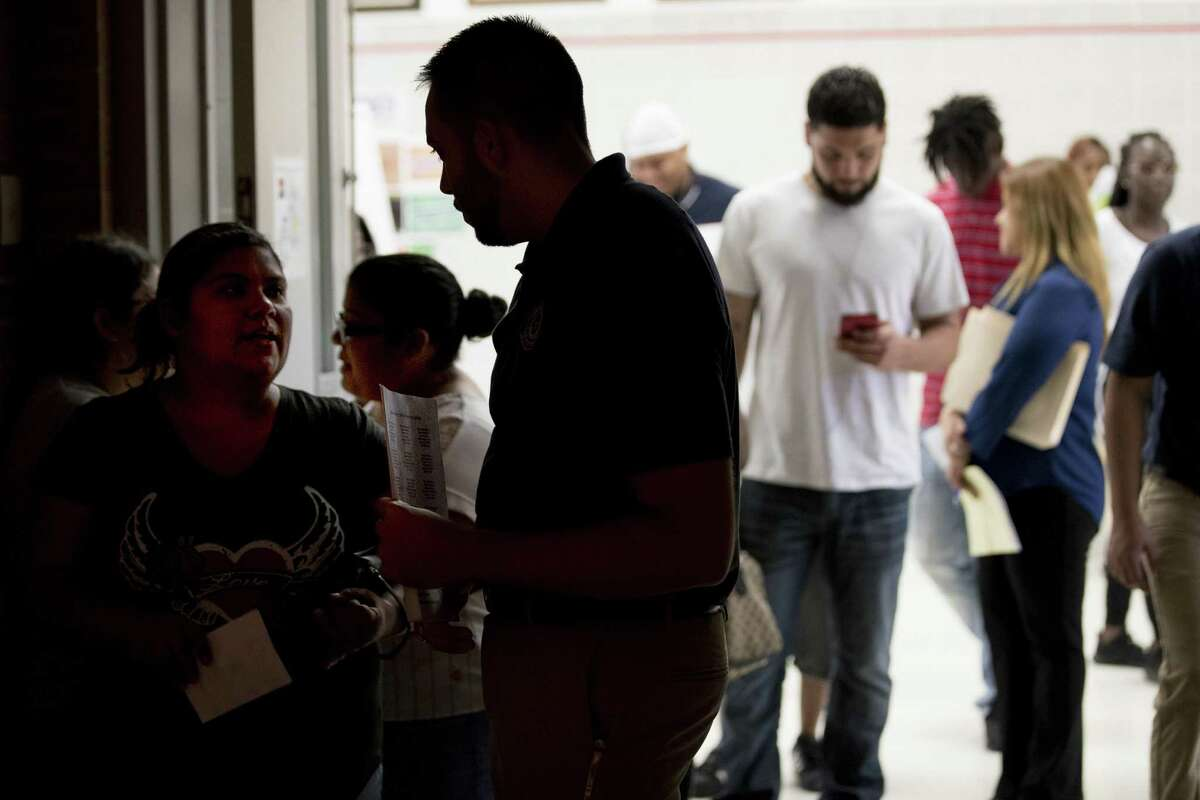 People line up for legal services during the Make It Right! program at North Shore High School on Saturday, July 14, 2018, in Houston. Make It Right! is designed to help members of the community, with low-level, non-violent misdemeanor offenses, have outstanding warrants removed and pending cases resolved with no immediate financial cost and no risk of arrest. ( Brett Coomer / Houston Chronicle )
