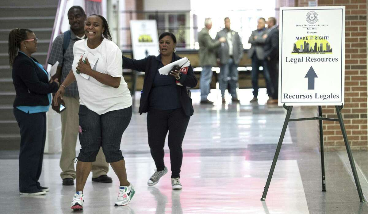 Keola Williams, left, celebrates after having eight outstanding tickets reduced to two, during the Make It Right! program at North Shore High School on Saturday, July 14, 2018, in Houston. Make It Right! is designed to help members of the community, with low-level, non-violent misdemeanor offenses, have outstanding warrants removed and pending cases resolved with no immediate financial cost and no risk of arrest. ( Brett Coomer / Houston Chronicle )