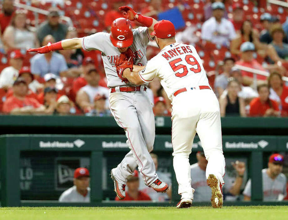 The Reds' Scooter Gennett, left, is tagged out by Cardinals relief pitcher Mike Mayers after being caught in a rundown between third and home in the sixth inning Saturday's game in St. Louis. Photo:       Jeff Roberson | AP Photo