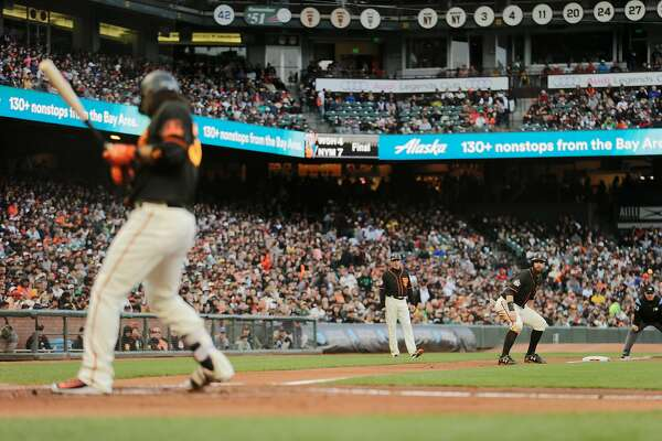 San Francisco Giants Brandon Belt (9) at third base watches as Giants Brandon Crawford (35) gets hit by a pitch during the second inning of an MLB game between the San Francisco Giants and Oakland Athletics at AT&T Park on Saturday, July 14, 2018, in San Francisco, Calif.