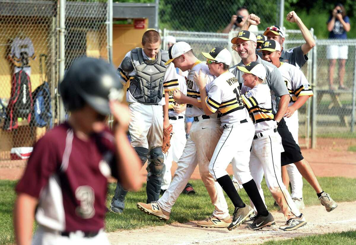 Lou Gehrig players mob relief pitcher Zach Worzel, center, after defeating North Haven's Max Sinoway squad 3-1 in the District 4 championship game in Milford on Saturday.