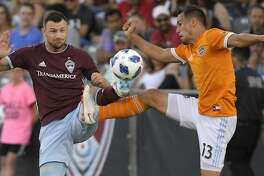 Colorado Rapids defender Tommy Smith, left, and Houston Dynamo midfielder Luis Gil try to kick the ball during the first half of a Major League Soccer match Saturday, July 14, 2018, in Commerce City, Colo. (AP Photo/Mark J. Terrill)
