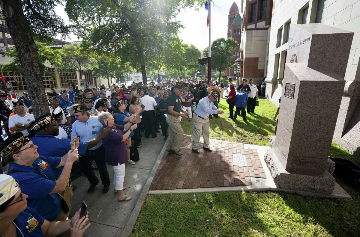 Attendees take photos of the new American Legion monument during its unveiling ceremony July 14, 2018, in front of the Cadena-Reeves Justice Center in downtown San Antonio.