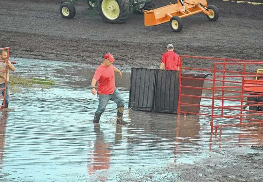 Morgan County fair crews try to repair the track in the Morgan County Fair Grandstand after rain caused flooding and mud Saturday. Photo:       Samantha McDaniel-Ogletree | Journal-Courier